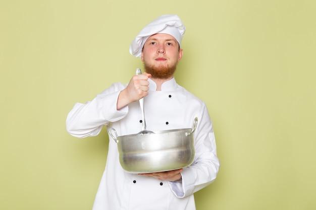 Ein junger männlicher koch der vorderansicht in der weißen kopfkappe des weißen kochanzugs, der silbernen topf und löffel hält