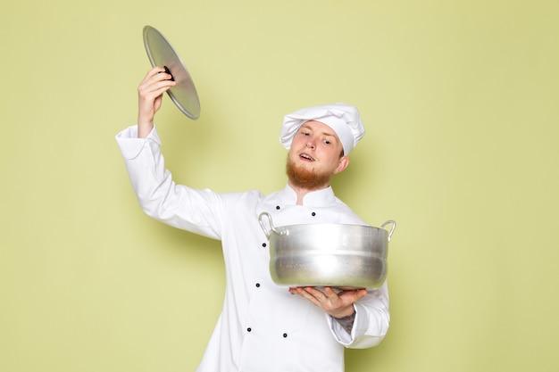 Ein junger männlicher koch der vorderansicht in der weißen kopfkappe des weißen kochanzugs, der silbernen topf und seine kappe hält