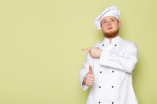 Ein junger männlicher koch der vorderansicht in der weißen kopfkappe des weißen kochanzugs, der zeigt