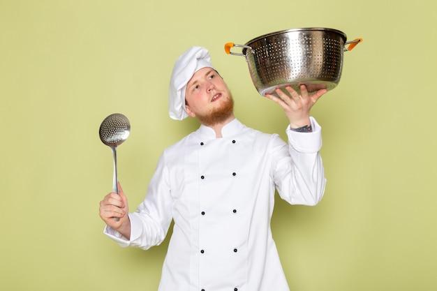 Ein junger männlicher koch der vorderansicht in der weißen kopfkappe des weißen kochanzugs hält silbernen und metallischen topf mit großem silbernem löffel