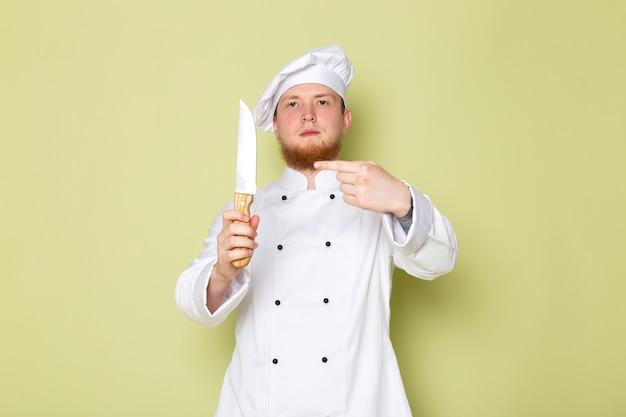 Ein junger männlicher koch der vorderansicht in weißem kopfkappen-haltemesser des weißen kochanzugs