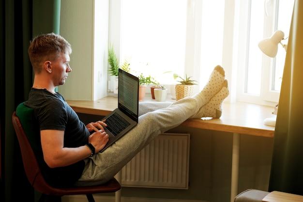Ein junger männlicher programmierer arbeitet zu hause mit einem laptop