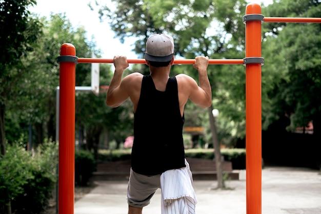 Ein junger männlicher sportler macht klimmzüge auf dem street-workout-spielplatz