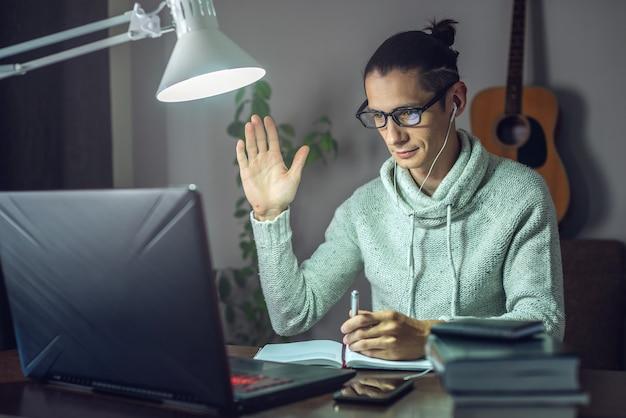 Ein junger männlicher student lernt nachts in einer online-lektion mit einem laptop im licht einer lampe im raum