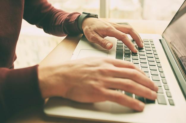 Ein junger mann arbeitet an seinem laptop
