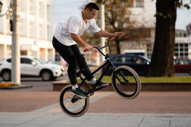 Ein junger mann auf einem bmx-bike wickelt das lenkrad in einen sprung. für jeden zweck.