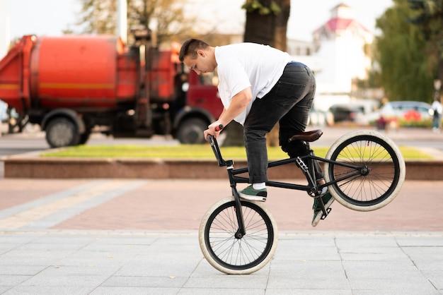 Ein junger mann auf einem bmx-rad fährt auf dem vorderrad und bremst mit dem fuß. für jeden zweck.