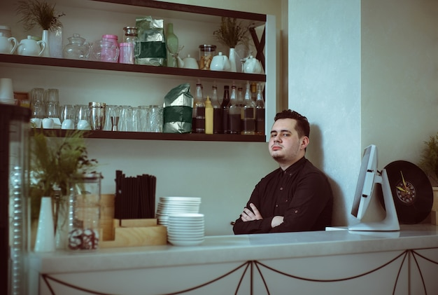 Ein junger mann barista im schwarzen hemd mit gekreuzten händen