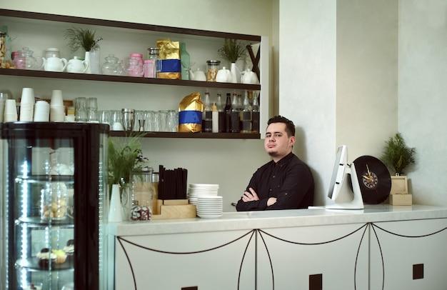 Ein junger mann barista in einem café hinter der bar