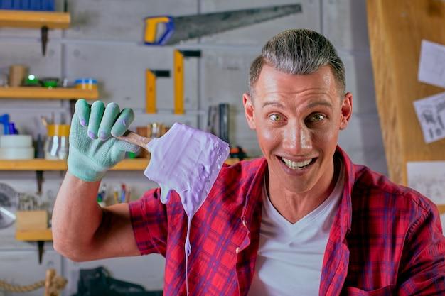 Ein junger mann bei der arbeit. maler mit einem pinsel. konzept der reparatur