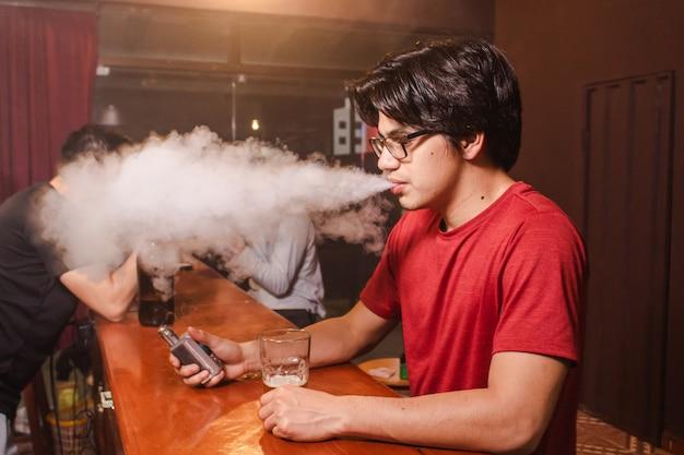 Ein junger mann bläst eine dampfwolke an der bar.