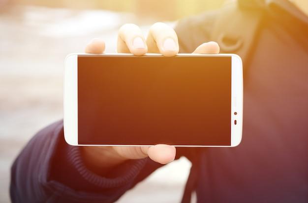 Ein junger mann demonstriert eine smartphone-anzeige