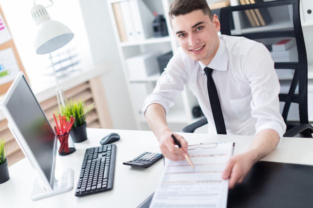 Ein junger mann, der an einem computertisch im büro sitzt und mit dokumenten arbeitet.
