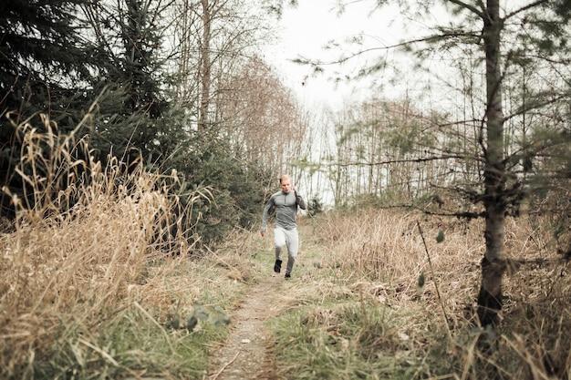 Ein junger mann, der auf spur durch wald läuft