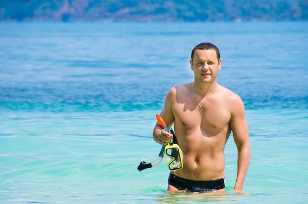 Ein junger mann, der aus das meer herauskommt, nachdem er geschwommen ist.