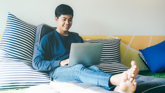 Ein junger mann, der computertablette am haus verwendet.