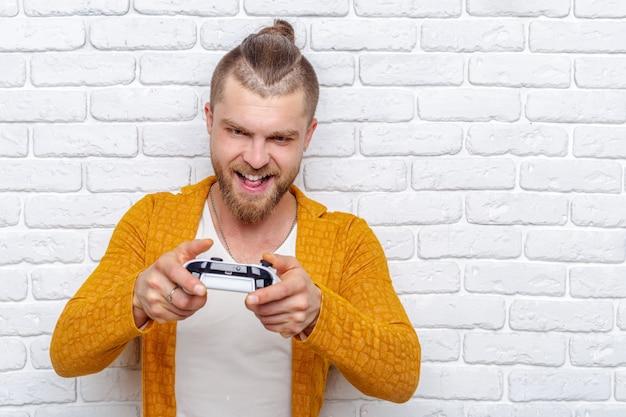 Ein junger mann, der den gamecontroller spielt videospiele hält