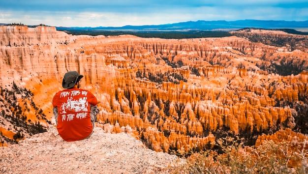 Ein junger mann, der den nationalpark von bryce point aus beobachtet
