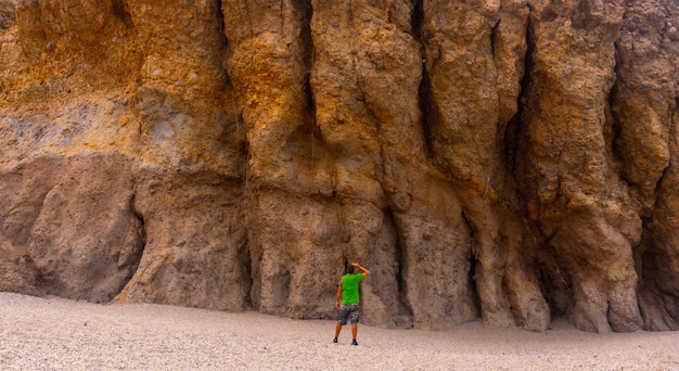 Ein junger mann, der die schönen natürlichen mauern von playa de los muertos im naturpark von cabo de gata, nijar, andalusien besucht. spanien