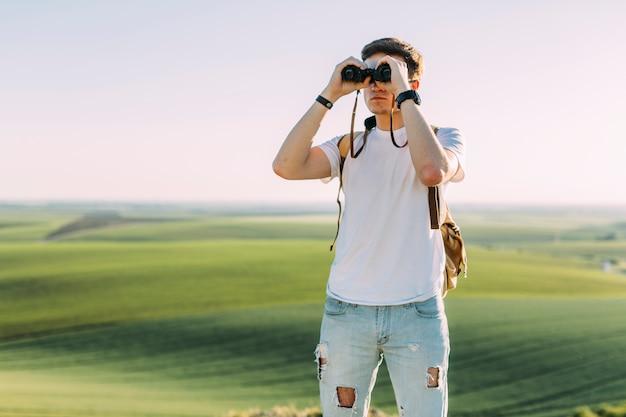 Ein junger mann, der durch binokulares gegen grasartiges land schaut