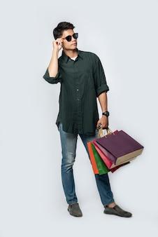 Ein junger mann, der ein dunkles hemd und jeans trägt, trägt viele taschen, um einkaufen zu gehen