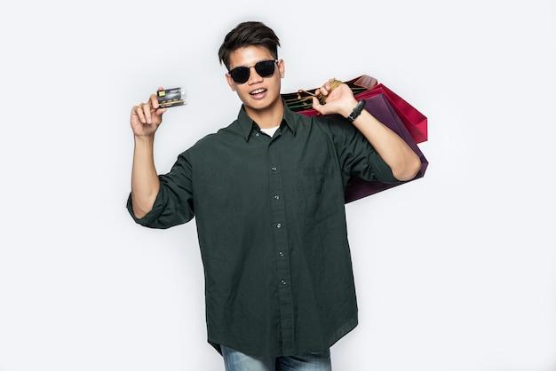 Ein junger mann, der ein dunkles hemd und jeans trug, trug mehrere taschen, um mit einer kreditkarte einkaufen zu gehen
