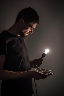 Ein junger mann, der eine brennende glühbirne in der hand auf schwarzen hintergrundkonzeptideen hält