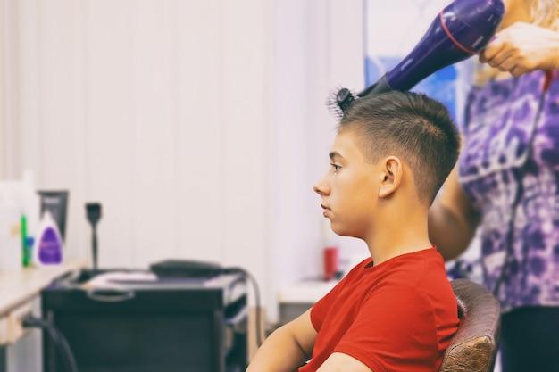 Ein junger mann, der eine modische frisur in einem friseurladen macht