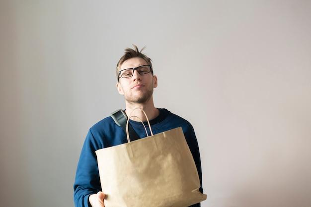 Ein junger mann, der eine papiertüte hält, liefert das produkt