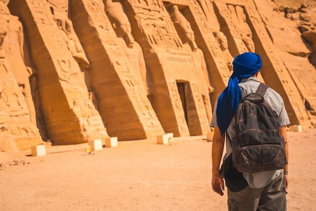 Ein junger mann, der einen blauen turban trägt, der den ägyptischen tempel von nefertari in der nähe von abu simbel in südägypten in nubien neben dem nassersee besucht. tempel des pharao ramses ii., reiselebensstil
