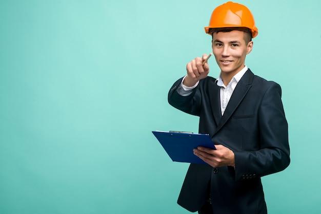 Ein junger mann, der einen schutzhelm trägt und einen zwischenablagepunkt an der kamera auf blauem hintergrund trägt