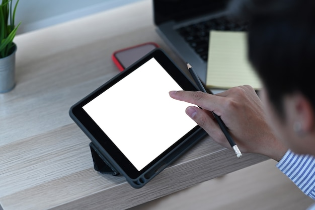 Ein junger mann, der freiberuflich auf dem bildschirm digitales tablet berührt, während er in neuem projekt zu hause arbeitet.