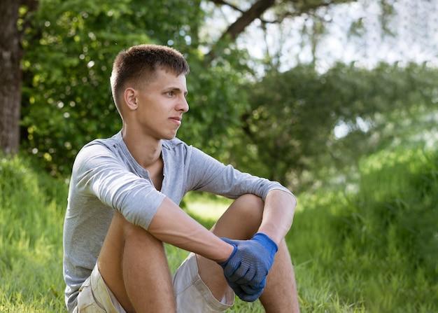 Ein junger mann, der freiwillig den park von müll befreit hat, sitzt mit handschuhen, die nach der arbeit ruhen, im gras