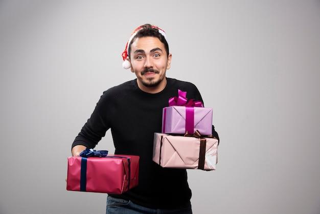 Ein junger mann, der geschenkboxen über einer grauen wand hält.