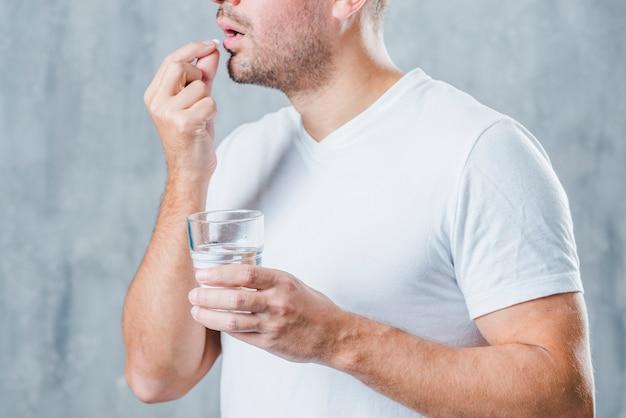 Ein junger mann, der glas wasser nimmt medizin hält