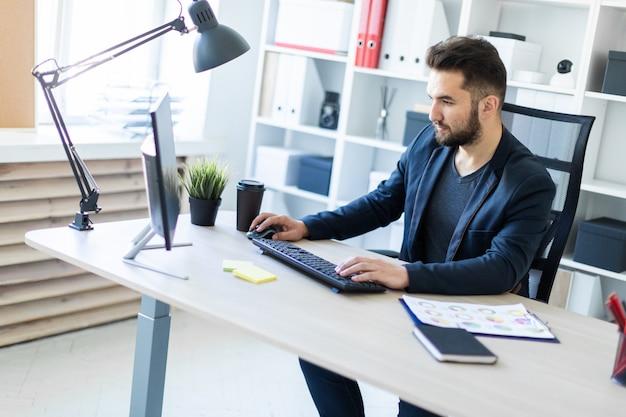 Ein junger mann, der im büro am computer arbeitet.