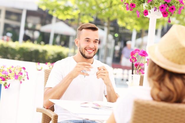 Ein junger mann, der im sommer mit einem date im café sitzt