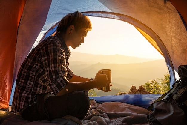 Ein junger mann, der im zelt mit dem halten der kaffeetasse sitzt