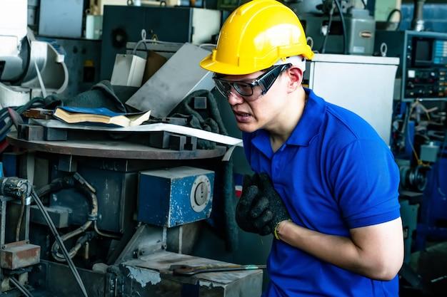 Ein junger mann, der in der fabrik arbeitet und sich an die brust klammert