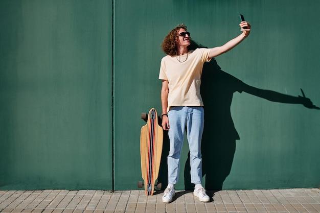 Ein junger mann, der mit einem smartphone ein selfie mit seinem skate und einer grünen wand hinter sich macht