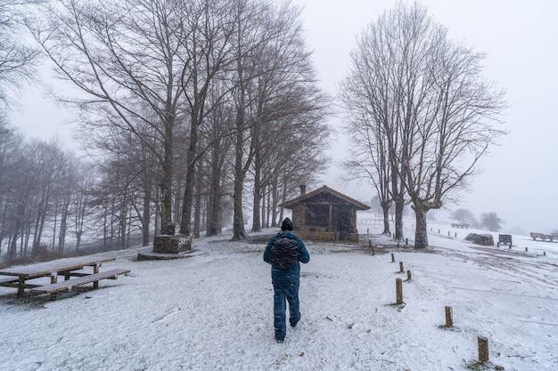 Ein junger mann, der neben der zuflucht des berges aizkorri in gipuzkoa geht. schneelandschaft im winter schneit