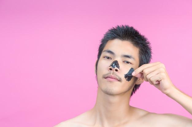 Ein junger mann, der seine hände verwendet, um schwarze kosmetik auf seinem gesicht auf einem rosa zu entfernen.