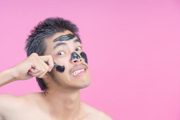 Ein junger mann, der seine hände verwendet, um schwarze kosmetik auf seinem gesicht mit den schmerz auf einem rosa zu entfernen.