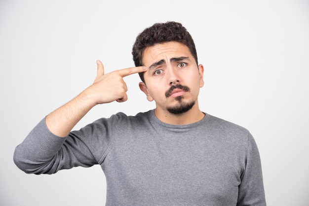 Ein junger mann, der seinen finger in den kopf steckt.