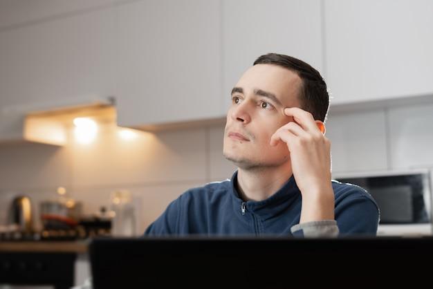 Ein junger mann, der tief in gedanken schaut, während er online mit laptop am schreibtisch in seiner wohnung arbeitet