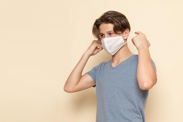 Ein junger mann der vorderansicht im grauen t-shirt, das eine maske trägt
