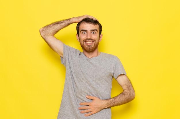 Ein junger mann der vorderansicht im grauen t-shirt, das lächelnd und auf der gelben wandmann-farbmodell-emotionskleidung posiert