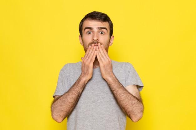 Ein junger mann der vorderansicht im grauen t-shirt, das mit schockiertem ausdruck auf den gelben wandmann-farbemotionen aufwirft