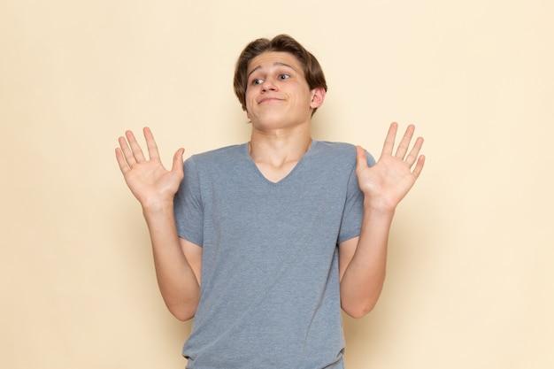 Ein junger mann der vorderansicht im grauen t-shirt, das mit verwirrtem ausdruck aufwirft