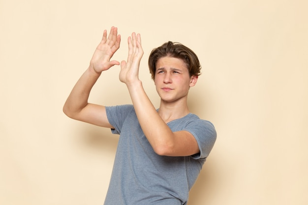 Ein junger mann der vorderansicht im grauen t-shirt, das mit vorsicht aufwirft